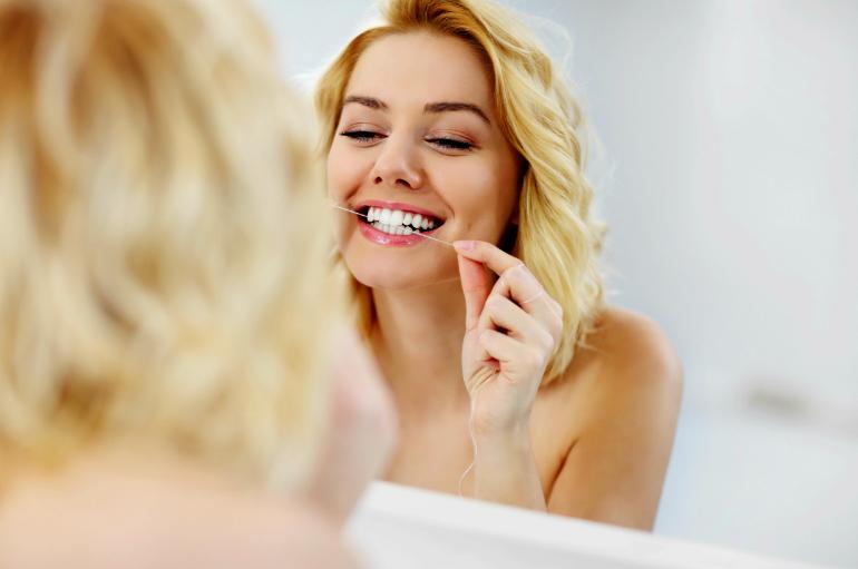 Odontología Preventiva en Villanueva del Pardillo - Mujer usando hilo dental